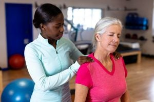 Female physiotherapist giving back massage to active senior woman in sports center
