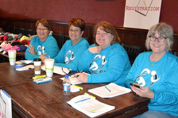 Event volunteers at registration table for the APDA Wisconsin half marathon. There were lots of laughs and story sharing between getting everyone signed in.